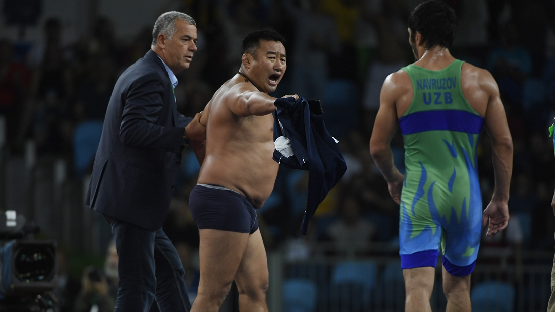 RIO DE JANEIRO, BRAZIL - AUGUST 21: Mongolian coach Bayaraa Byambarinchin strips down to his underpants in protest and shouts Ikhtiyor Navruzov of Uzbekistan after he defeated Byambarinchin's wrestler Ganzorigiin Mandakhnaran to capture bronze during men's 65kg freestyle wrestling on Sunday, August 21, 2016. (Photo by AAron Ontiveroz/The Denver Post via Getty Images)